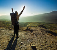 Girl with hands up in the mountains against sun Stock Images