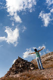Girl with hands up near the pile of stones Stock Images
