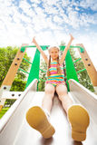 Girl with hands up sits on playground chute Royalty Free Stock Photo