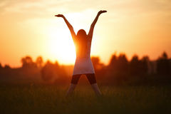 Girl with hands up on sunset background Stock Photos