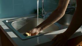 Girl hands wash sink in kitchen with foamy sponge. Closeup girl nice hands wash steel sink using foamy sponge in modern kitchen with blue walls stock video footage