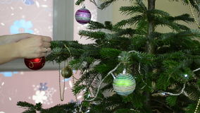 Girl hang decorative toy ball on Christmas tree branch stock video footage