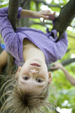 Girl hang from a tree in the backyard Stock Photos
