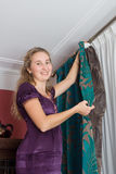 Girl hang up a curtain Royalty Free Stock Photography
