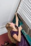 Girl hang up a curtain Stock Photos