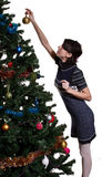 Girl hanging ball on christmas tree Royalty Free Stock Photo