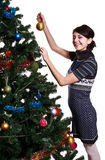 Girl hanging ball on christmas tree Royalty Free Stock Image