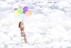 Girl hanging on balloons flying in the clouds Stock Photography