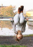 Girl hanging on banisters. Exercising little kid - girl in grey clothes and brown shoes hanging on banisters in front of pond stock photography