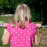 Girl hanging on bar Stock Image