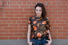 Girl hanging on brick wall. Twenty something fashion model giving a piercing look to the camera while hanging on a brick wall Stock Photo