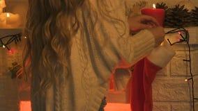 Girl hanging Christmas stocking on mantelpiece of fireplace, festive decoration stock footage