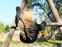 Girl hanging on climbing frame Stock Images
