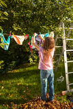 Girl hanging clothes on clothesline at garden Royalty Free Stock Image