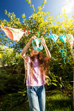 Girl hanging clothes with clothespins at sunny day Stock Photos