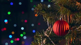 A girl is hanging decorating Christmas decoration on Christmas tree, close up shot, with sparking LED lamp lighting spot in the da stock video footage