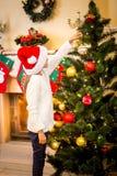 Girl hanging decorative ball on Christmas tree Stock Image
