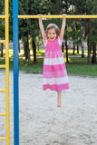 Girl hanging on a horizontal bar Royalty Free Stock Photography