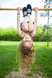 Girl hanging on horizontal bar Royalty Free Stock Photo