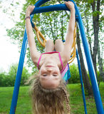 Girl hanging on horizontal bar Stock Photo