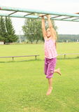 Girl hanging on obstacle course Royalty Free Stock Image