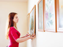 Girl hanging  pictures in frames on wall Royalty Free Stock Photos
