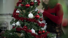 Girl hanging ribbons on Christmas tree in slow motion. Young romantic couple decorating Christmas tree by a fireplace with red and silver ornaments, red, blue stock footage