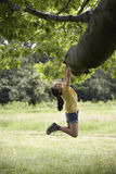Girl Hanging From Tree Branch Stock Photo