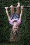 Child hanging upside down on climbing frame. Girl spinning around  and exercising on an outdoor climbing frame, looking at camera Stock Photography