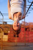 Girl hanging upside down on gymnastics rings Stock Photos