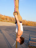 Girl hanging upside down on gymnastics rings Royalty Free Stock Photo
