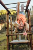 Girl hanging upside down on a horizontal ladder in a park. Girl hanging heads down in a park holding a heart shaped candy lollipop. Girl playing in a park stock photo