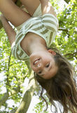Girl Hanging Upside Down From Tree Stock Photo