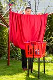 View of a girl working in the backyard. Girl is hanging the washed red sheets up in the garden Stock Photo