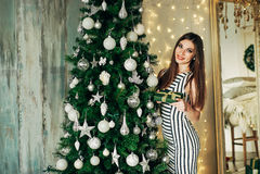 Girl hangs on a Christmas tree ball Stock Image