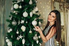 Girl hangs on a Christmas tree ball Stock Photos