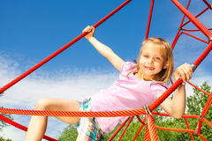 Girl hangs on red net ropes with two arms Stock Images