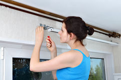 Girl hangs vertical blinds, tighten with a screwdriver, screw br Royalty Free Stock Photo