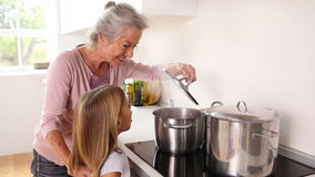 Girl happily cooking with her grandmother stock footage