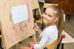 Girl happily looks into frame on a drawing lesson Stock Images