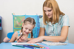 Girl happily looks at painted with the help of drawing the line Royalty Free Stock Photo