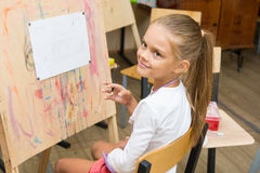 Girl happily looks at the teacher at drawing lesson Stock Image