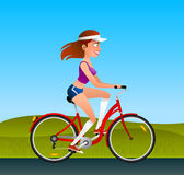 Girl happily riding a red bicycle Stock Image
