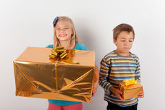 Girl happy with a big present box but her brother has only a sma Stock Image