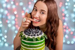 Girl with happy birthday cake. Beautiful girl tasting happy birthday cake by licking her finger with cream on festive light background royalty free stock photography