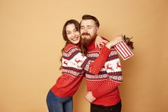 The girl is happy with the guy giving her a Christmas gift both are dressed in red and white sweaters with deer and stock images