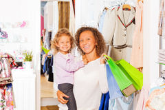 Girl with happy mother holding bags while shopping Stock Photo