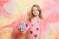 Girl, happy small child with rabbit toy and pink heart Stock Photo