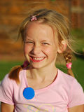 Girl happy smiling. Outdoor portrait of a happy smiling Caucasian girl child wearing a blank blue button on her pink shirt stock photo