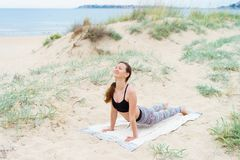 Girl happy and smiling doing yoga asanas on the sand of the sea stock photography